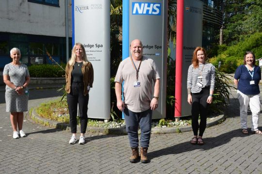 The five members of the Enhanced Supportive Care team stand outside a hospital building