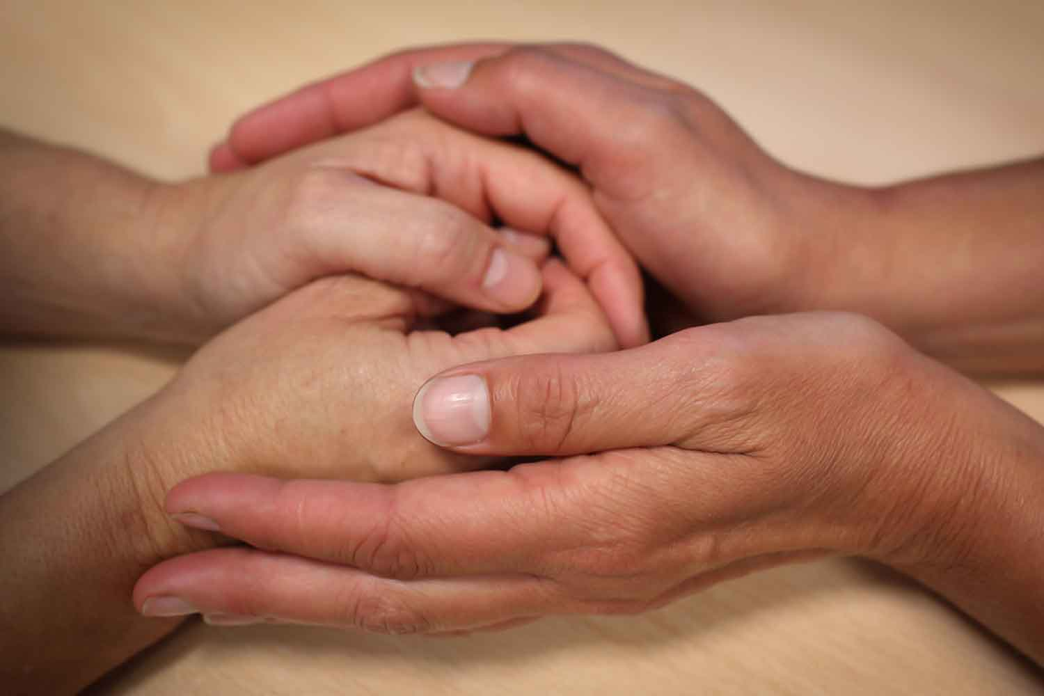 A person's hands wrapped in another person's hands giving support
