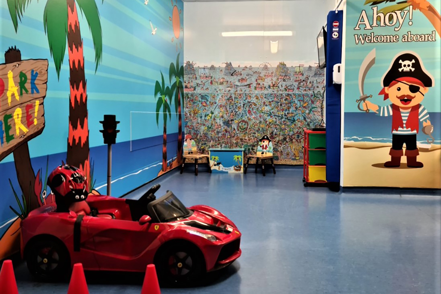 a small, ride-on electric car parked in a colourfully decorated children's waiting area