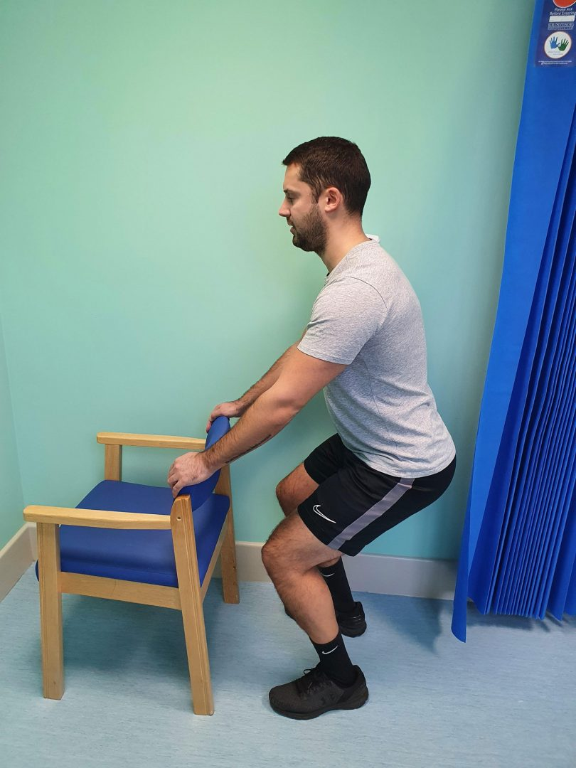Person standing hip width apart and doing a half squat exercise