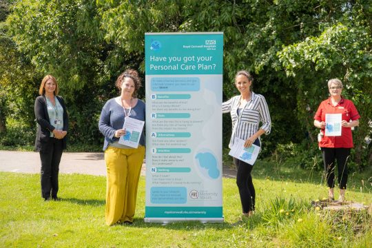 Four colleagues from maternity services stand around a pull-up banner displaying copies of the new personalised care plan