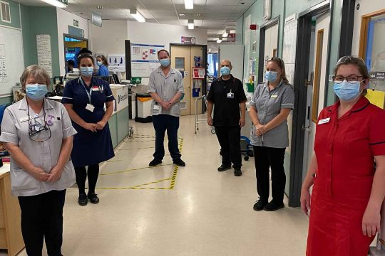 Staff gathered at ward reception wearing masks and practising social distancing
