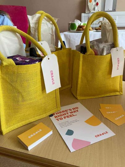 Little yellow comfort bags filled with wrapped items, displayed alongside a flyer and business cards