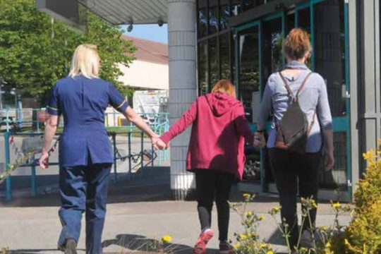 Snippet of the book cover depicting a member of the safeguarding team, a parent/guardian and a child walking towards the front entrance of the hospital on a sunny day.