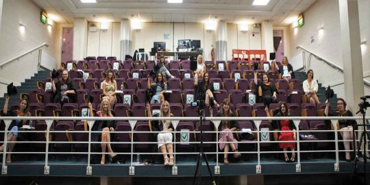 In the auditorium at Truro College, a socially distanced cohort of seated midwives raise their graduation caps in celebration