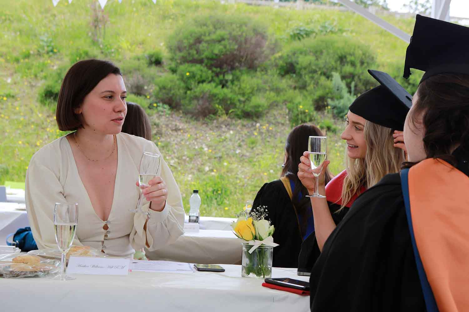 A small group of new midwifery graduates and guests enjoy a catered reception outside Truro college