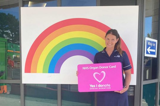 Specialist Organ Donation Nurse holding a large organ donation card outside entrance to hospital