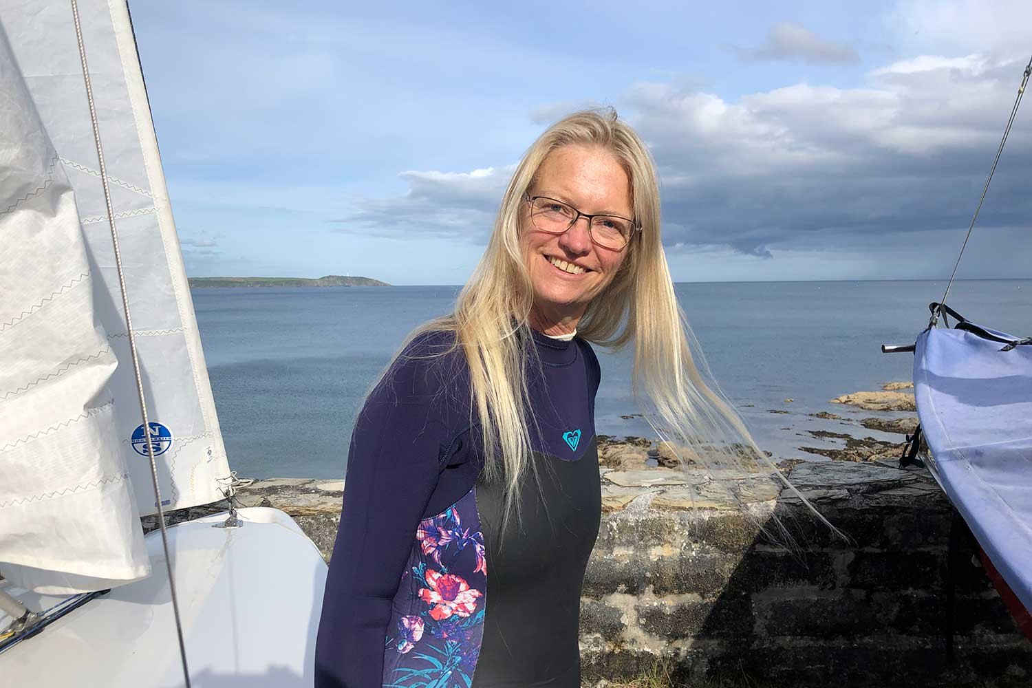 Research patient Jan Barnes standing on a quay next to sailing boat