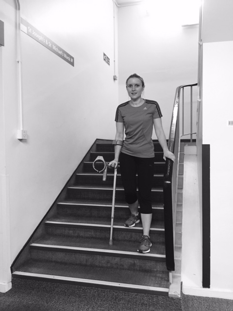 Person walking down stairs using crutches