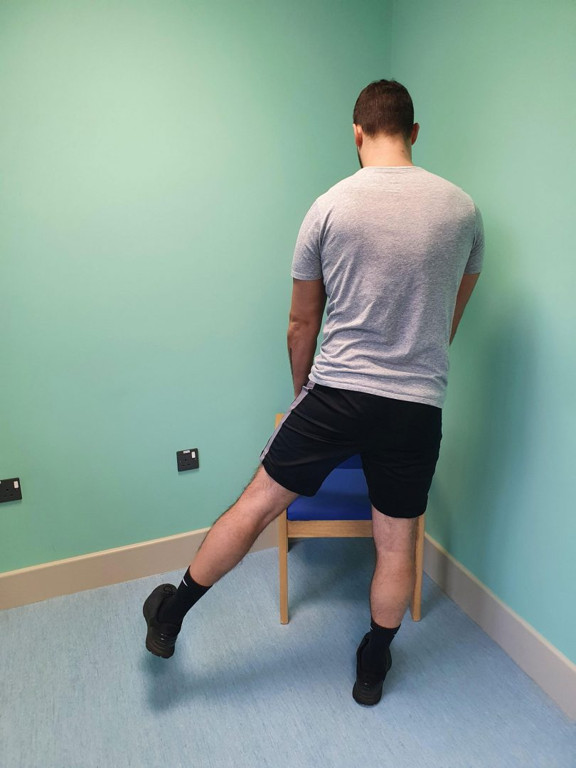 Person doing a standing hip abduction exercise using a chair for support