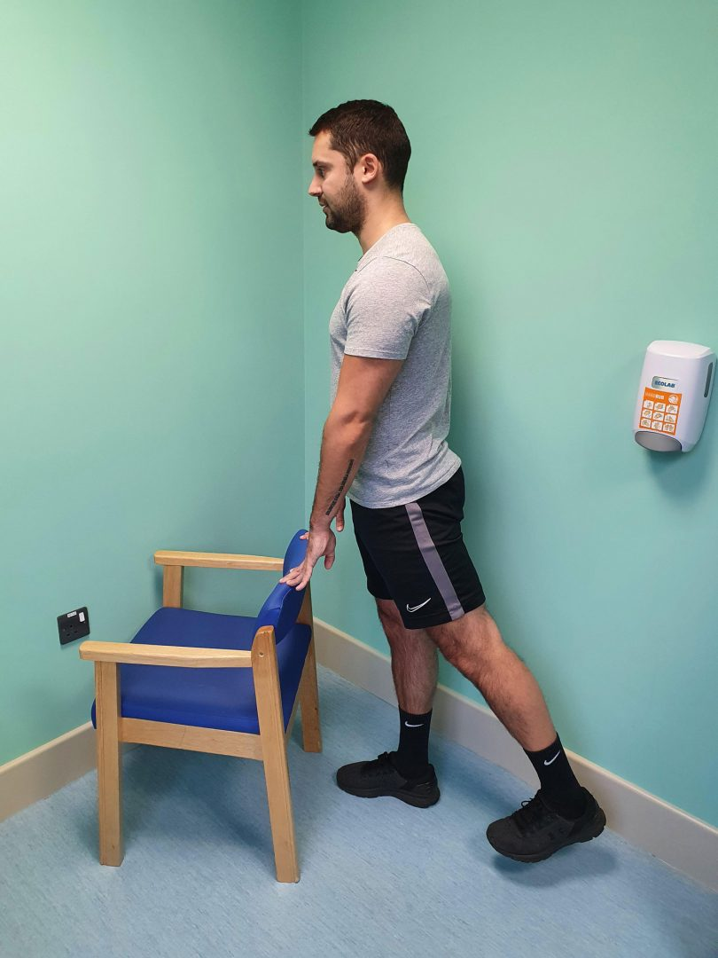 Person who has had a dynamic hip screw operation doing a standing hip extension exercise using a chair for support