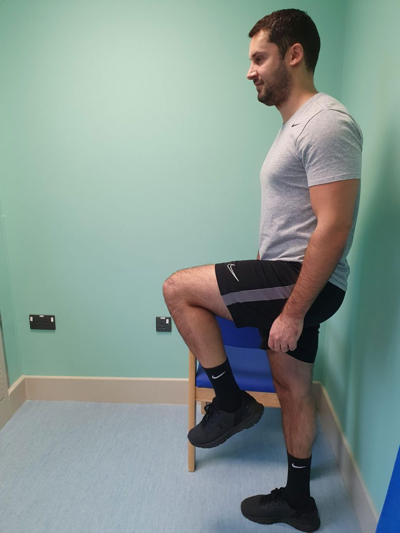 Person doing a hip flexion exercise using a chair for support