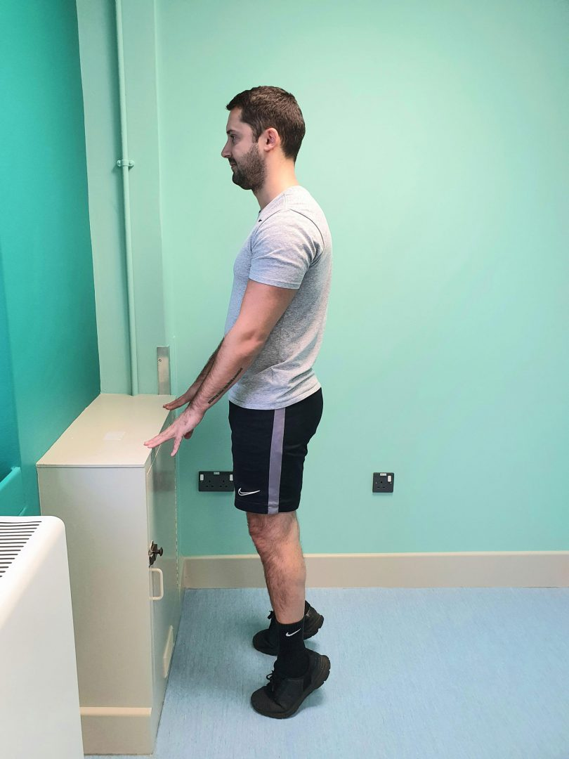Person standing doing a supported calf raise exercise