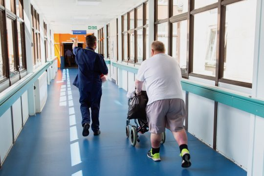 Member of staff walking through corridor with patients