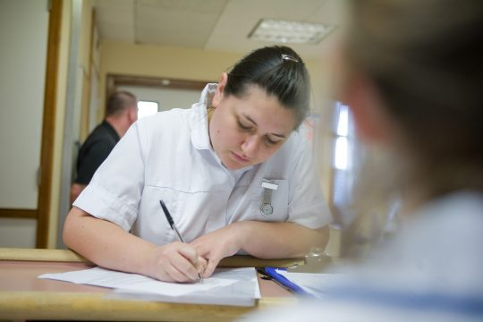 Medical staff member in uniform filling in a document
