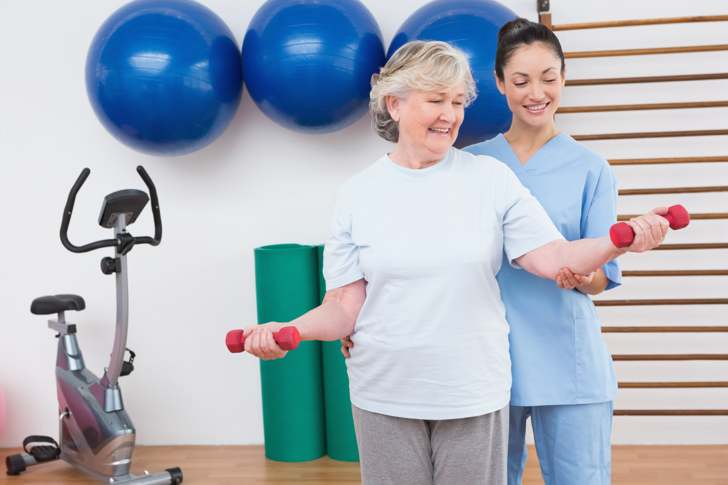 Clinician with patient using small weights in physio