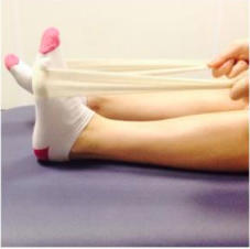 Person doing ankle stretching exercises by pointing and flexing their toes using a towel or bandage step 1