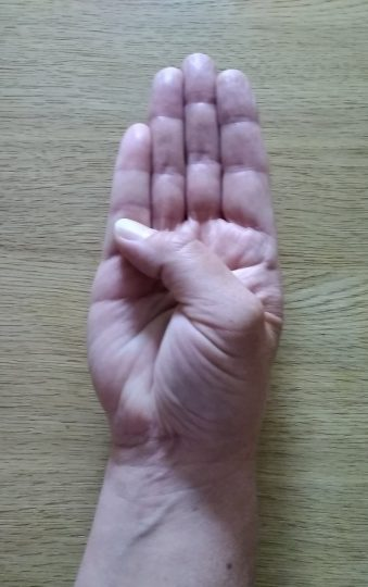 Person with the back of their hand on a table moving their thumb to meet the base of their little finger