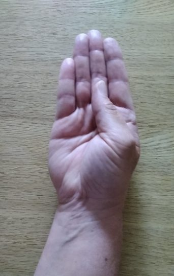 Person with the back of their hand on a table moving their thumb to meet the base of their second finger
