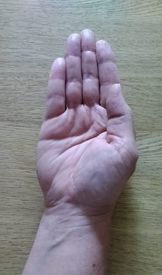 Person with the back of their hand on a table with the hand slightly cupped