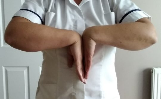Person standing with their hands in a reverse prayer position