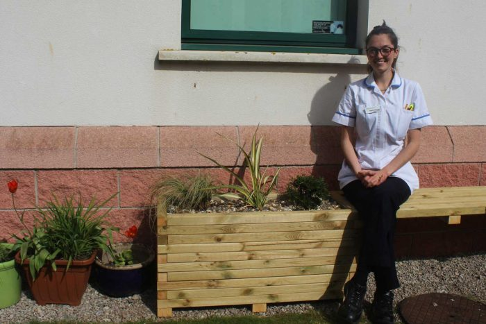 Uniformed radiographer sits outside on a bench surrounded by plants