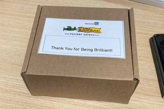 """Small cardboard box placed on a desk. The box includes a label featuring the logo of the Patient Safety team and the words """"Thank you for being brilliant."""